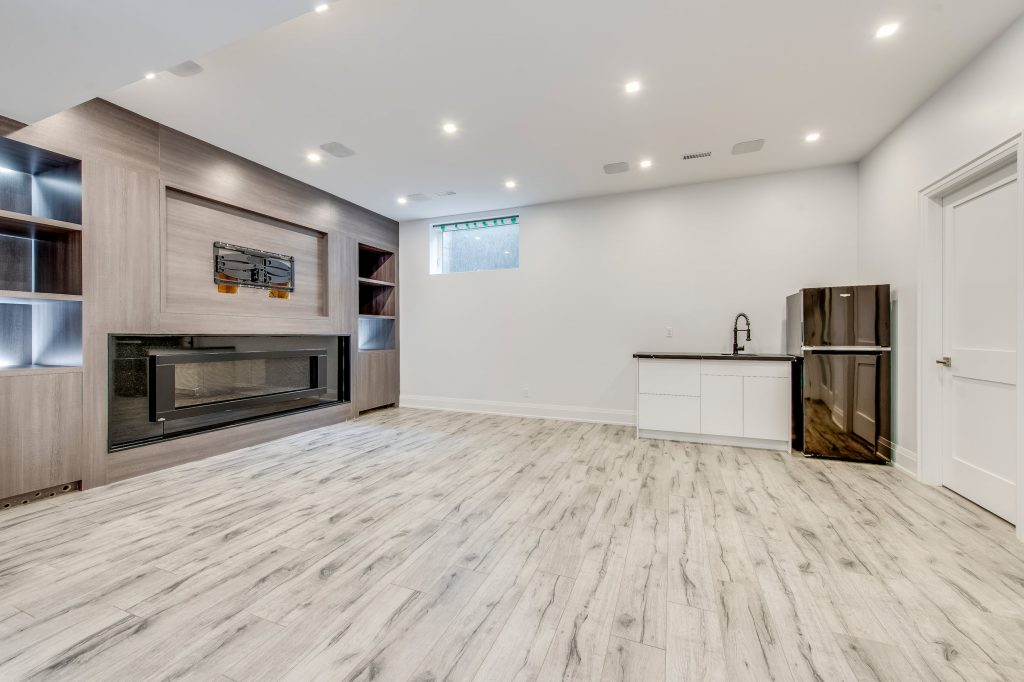 amazing basement family room with entertainment unit and small kitchen