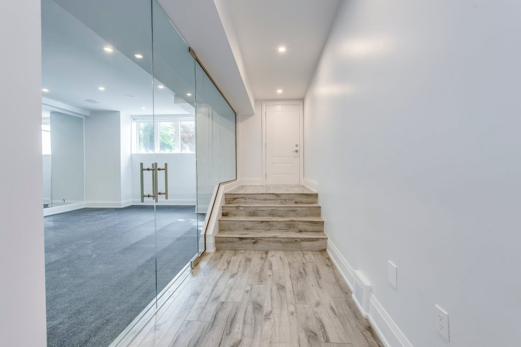 Amazing Hallway with Wooden Flooring and Glass Walls in Custom Basement Renovation