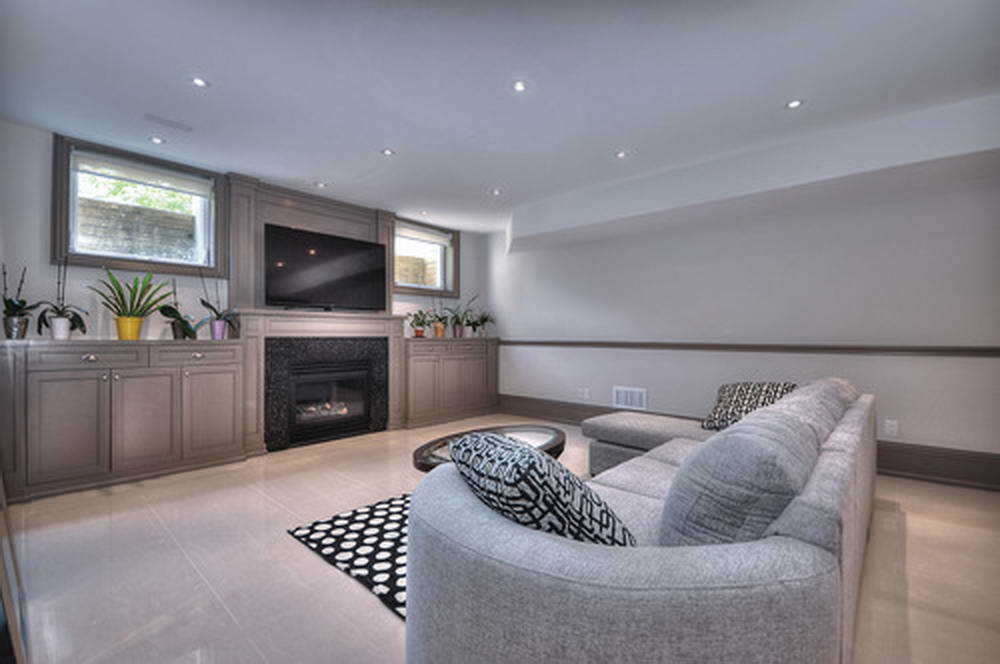 Modern Basement Living Room with Baseboard Trim and Wooden Floor by Moose Basements Remodeling Mississauga